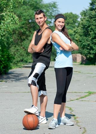 basketball girl: Joven pareja de gimnasio del hombre y la mujer jugando al aire libre de baloncesto