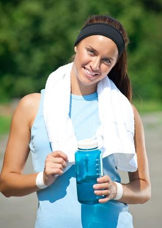 mujer deportista: Mujer joven con una toalla blanca y botella de agua tiene un descanso después de trotar en el parque Foto de archivo