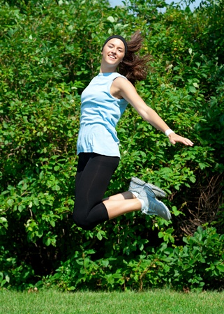 Young athletic woman jumping in air and smiling outdoors Stock Photo - 10947921