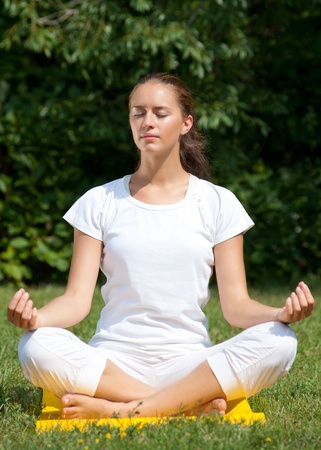 Young beautiful woman doing yoga meditation in park  photo