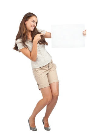 Portrait of a excited young woman holding a blank signboard and pointing, isolated on white background photo