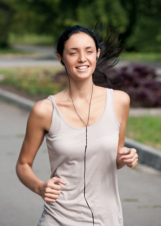 Young beautiful woman running in park and listening to music  Stock Photo