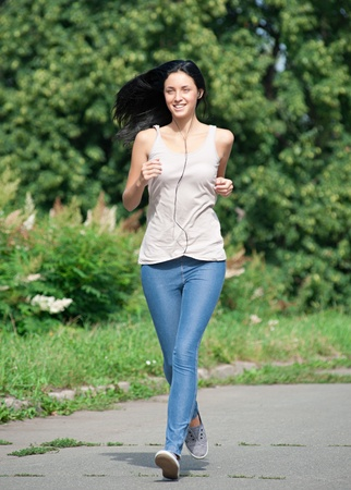 Young beautiful woman running in park and listening to music  photo