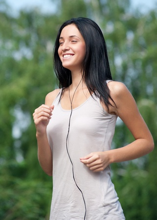 Young beautiful woman running in summer park  Stock Photo