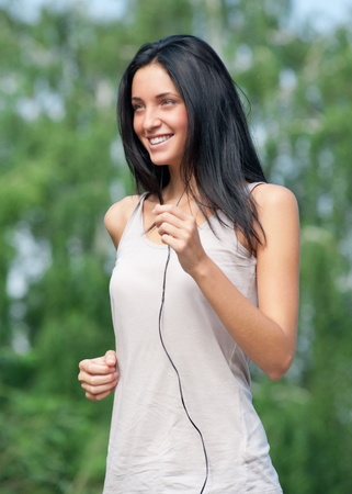 walking in park: Young beautiful woman running in park and listening to music  Stock Photo