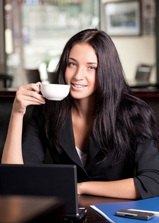 Portrait of young attractive business woman drinking coffee and using laptop photo