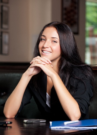 Portrait of young attractive business woman sitting in a cafe  photo