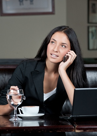 Portrait of young attractive business woman drinking coffee and talking on a cell phone photo