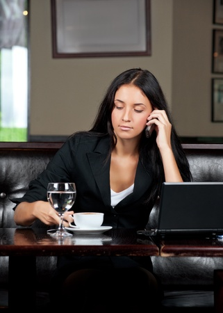 Portrait of young attractive business woman with cup of coffee talking a cell phone photo