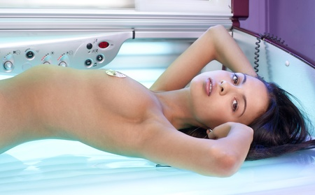 Young beautiful woman with slim body lying in tanning bed Stock Photo - 10948060