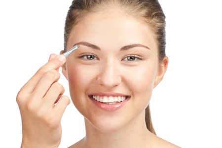 Young beautiful woman plucking her eyebrows with tweezers. Isolated on white background Stock Photo - 10948042