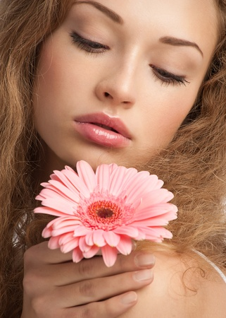 Close-up portrait of young beautiful woman with long curly hair holding pink flower Stock Photo - 10947647