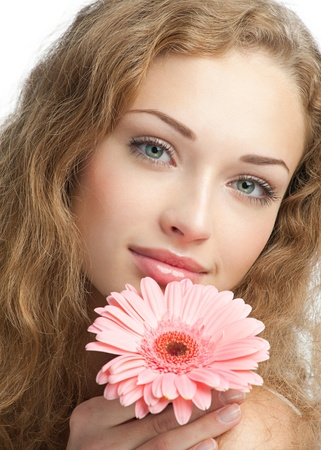 Close-up portrait of young beautiful woman with long curly hair holding pink flower. Isolated on white background photo