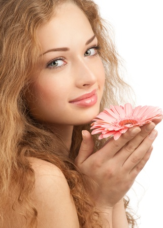 Close-up portrait of young beautiful woman with long curly hair holding pink flower. Isolated on white background Stock Photo - 10948015