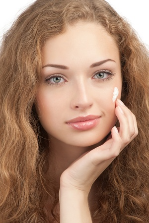 Portrait of young beautiful woman applying moisturizing cream on her face, isolated on white background photo