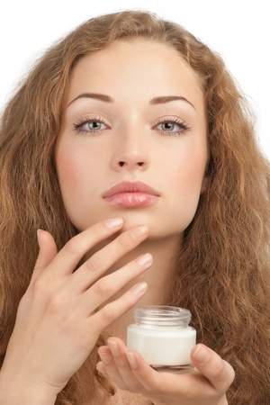 Portrait of young beautiful woman applying moisturizing cream on her face, isolated on white background Stock Photo - 10948013