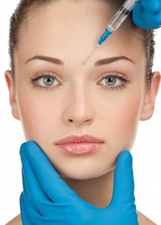 zastrzyk: Wstrzyknięcie botoksu kosmetyczne do ładnej kobiecej twarzy. Pojedynczo na białym tle