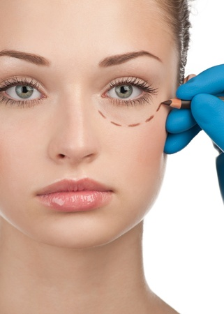 Beautiful young woman with perforation lines on her face before plastic surgery operation. Beautician touching woman face. Stock Photo - 10948068