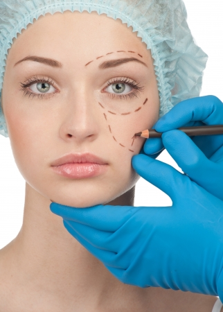 Beautiful young woman with perforation lines on her face before plastic surgery operation. Beautician touching woman face. Stock Photo - 10947991