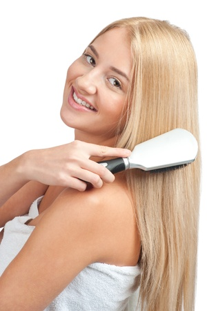 Portrait of young beautiful woman wearing white towel brushing her long straight blond hair photo
