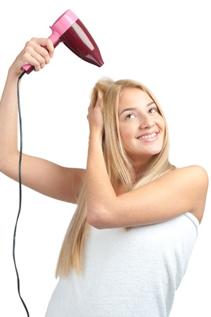 Portrait of prety young woman with long blond hair using hairdryer, isolated on white background photo