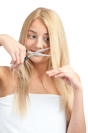 Young beautiful woman wearing white towel cutting her long blond hair with scissors, isolated on white background photo