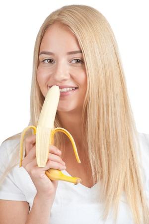 comiendo platano: Retrato de joven bella mujer con una larga rubia comiendo plátanos pelo, aisladas sobre fondo blanco
