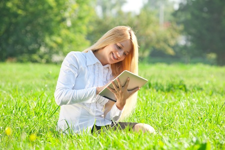 Young  business woman sitting on grass and using electronic tablet outdoors  photo
