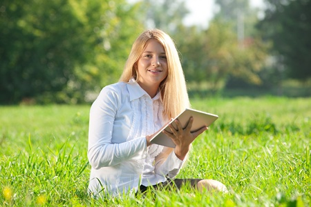 laptop outside: Young  business woman sitting on grass and using electronic tablet outdoors