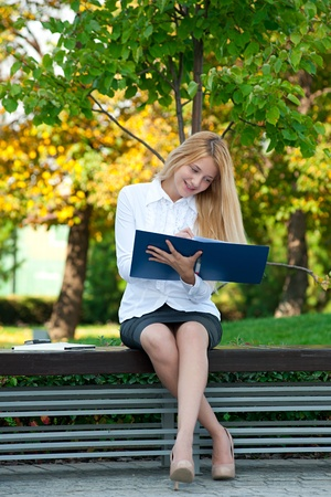 park bench: Young attractive business woman with documents sitting on a park bench