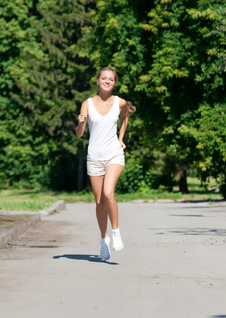 Young beautiful woman running in summer park  photo