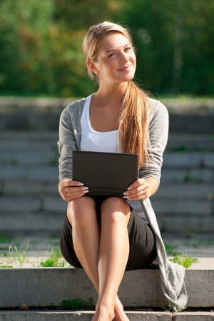 Young  business woman sitting on stairs and using laptop outdoors  Stock Photo