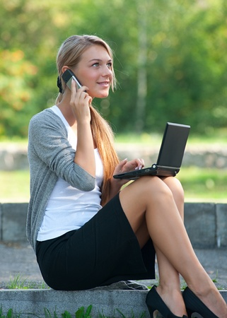 Young  business woman sitting on stairs and talking on a cell phone outdoors  photo