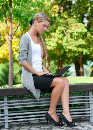 people sitting: Young  business woman sitting on a park bench and using laptop outdoors