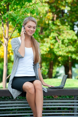 sitting on a bench: Young  business woman sitting on a park bench and talking on a cell phone outdoors