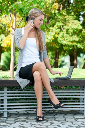 Young attractive business woman talking on a cell phone and using laptop outdoors