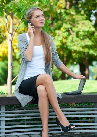 Young  business woman sitting on a park bench and talking on a cell phone outdoors  photo