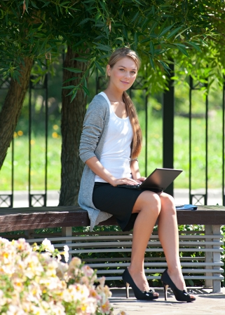 people sitting: Young  attractive business woman sitting on bench and using laptop outdoors