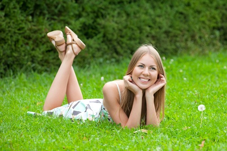 Young woman wearing summer dress lying on grass in park and smiling photo