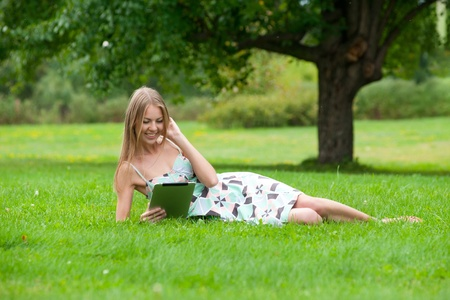 Young woman lying on grass and using electronic tablet outdoors  photo