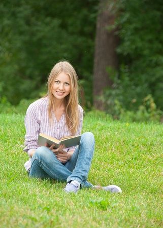 Pretty young woman sitting on the grass and reading book outdoors  photo