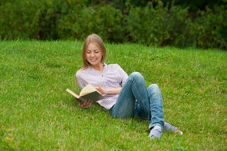 Pretty young woman lying on the grass and reading book outdoors  photo