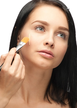 Portrait of beautiful young woman applying foundation on her face Stock Photo - 10997908