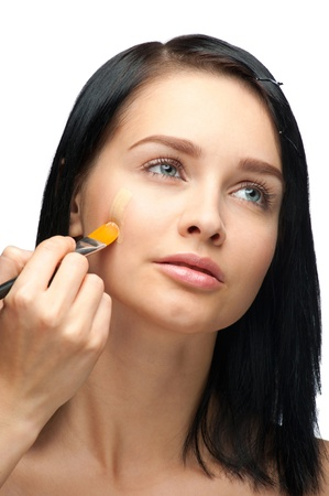 Portrait of beautiful young woman applying foundation on her face Stock Photo - 10998253