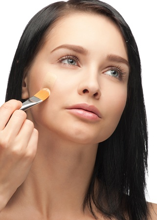 Portrait of beautiful young woman applying foundation on her face Stock Photo - 10997902