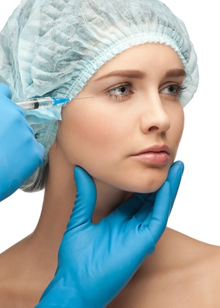 Cosmetic injection of botox to the female eyelid. Isolated on white background photo