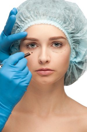 eyelid: Beautiful young woman with perforation lines on her face before plastic surgery operation. Beautician touching woman face. Stock Photo