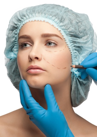 cheek: Beautiful young woman with perforation lines on her face before plastic surgery operation. Beautician touching woman face. Stock Photo