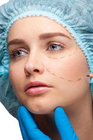 Beautiful young woman with perforation lines on her face before plastic surgery operation. Beautician touching woman face. Stock Photo - 10998282