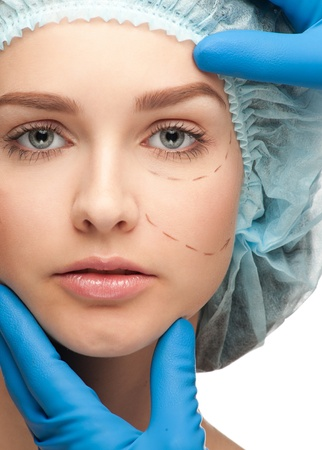 plastic glove: Beautiful young woman with perforation lines on her face before plastic surgery operation. Beautician touching woman face. Stock Photo